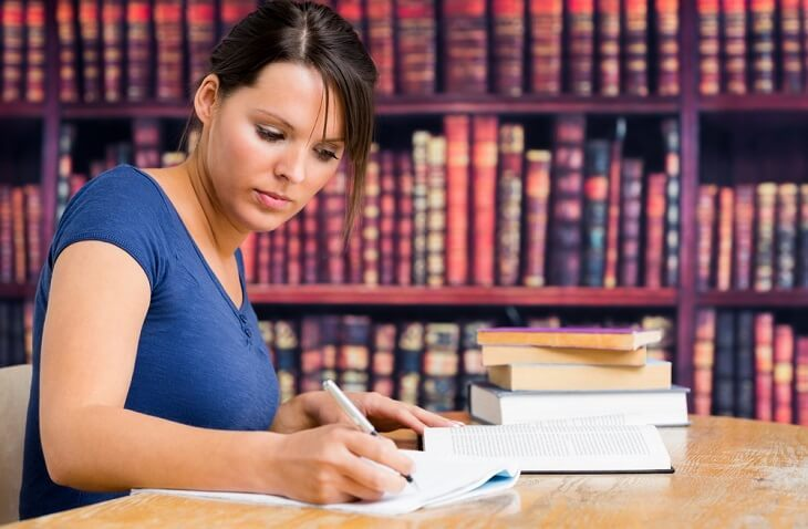 Female student studying in a library with law books in the background.