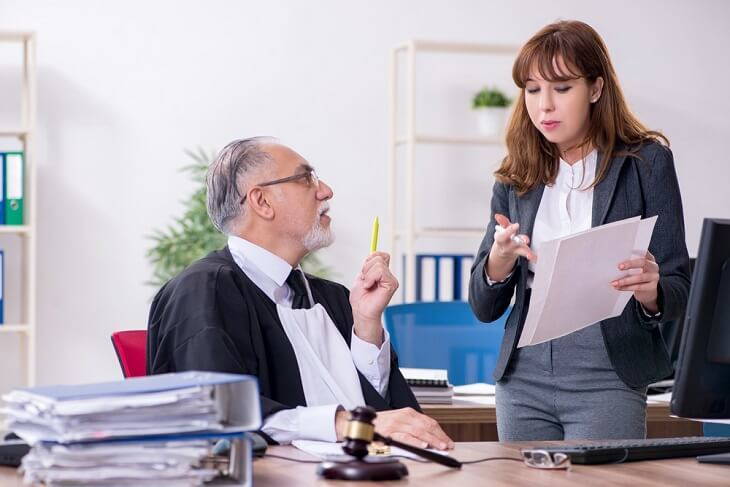 A male judge and female paralegal discussing legal paperwork in the judge's office.