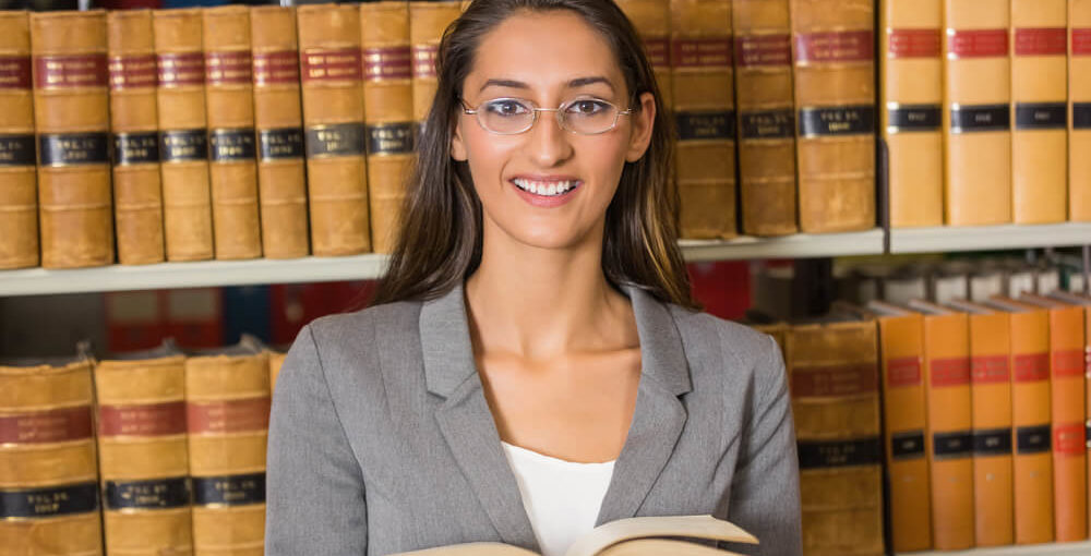 Female student reading law book in the law library