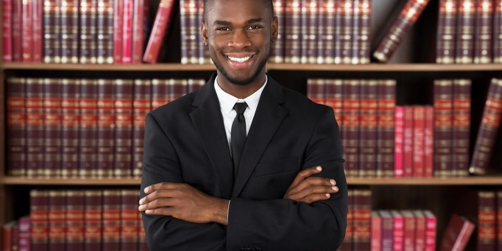 A young African American male law student in a law library.