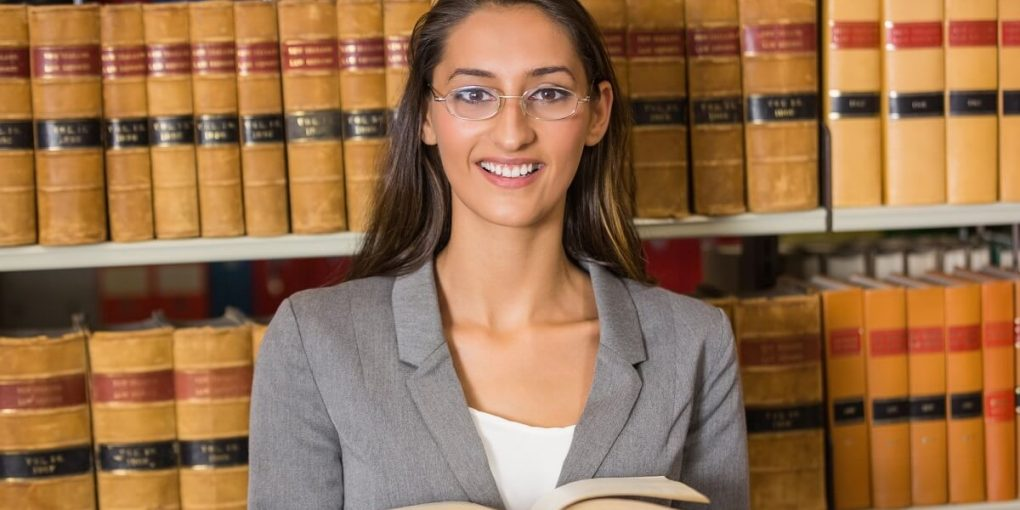 A young female paralegal studying at a law library.